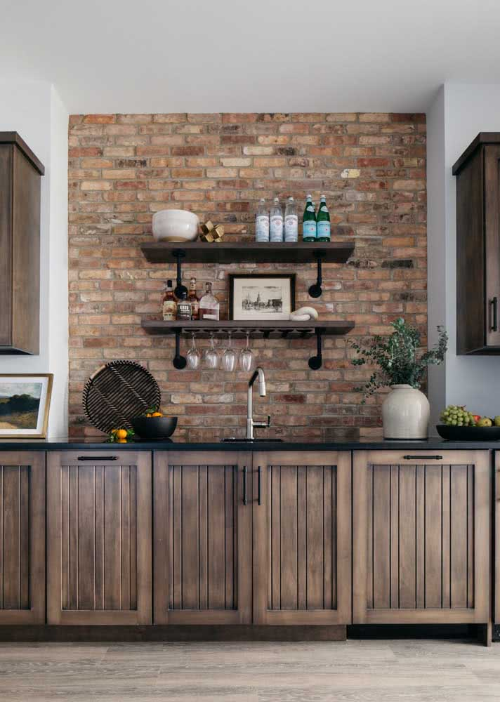 Cozinha com bancada de madeira e granito preto absoluto como material escolhido para o tampo.