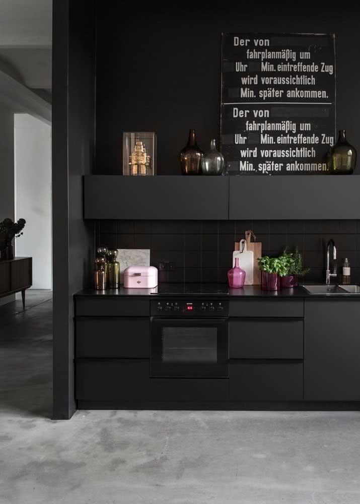 Cozinha preta com bancada de granito preto absoluto.