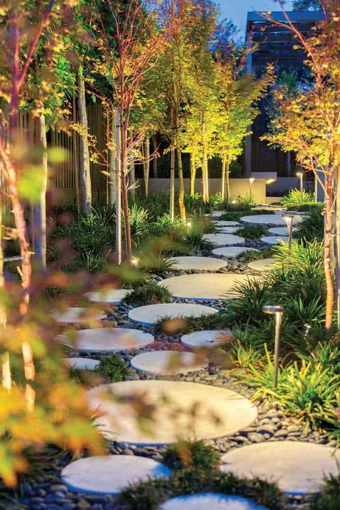 Caminho do jardim todo iluminado na entrada desta residência com pedras.