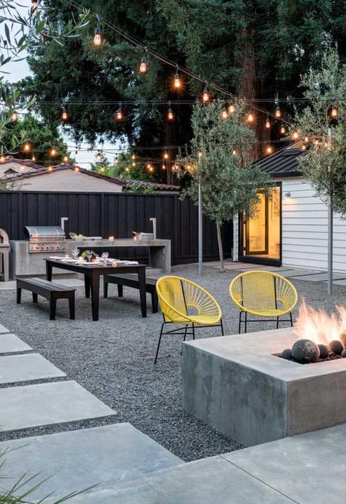 Área aconchegante para confraternizações e para receber convidados no quintal recebeu pedras no jardim.