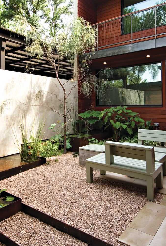 Jardim com pedras na área externa com fonte de água.