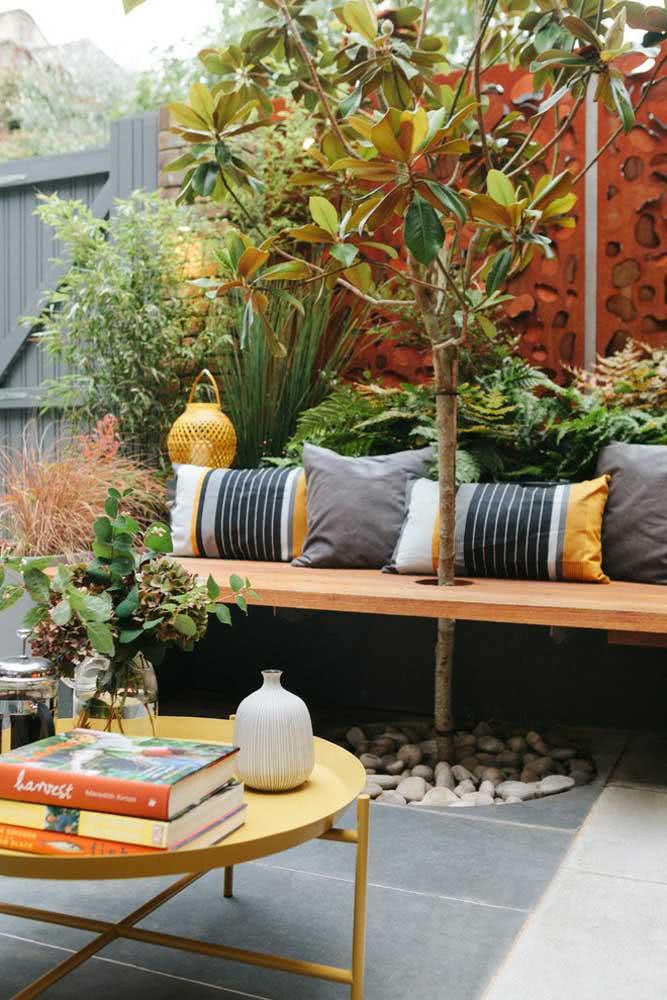 Área externa aconchegante com um pequeno espaço para o arbusto com pedras.