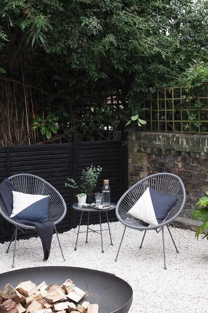 Área charmosa de convivência no jardim dos fundos da casa com pedras.