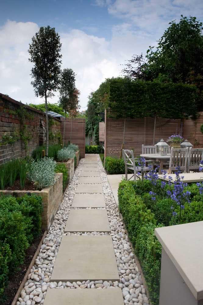 A pedra seixo é outra opção ideal para ser utilizada para decorar o seu jardim. Aqui ela percorre o caminho que conecta os espaços.