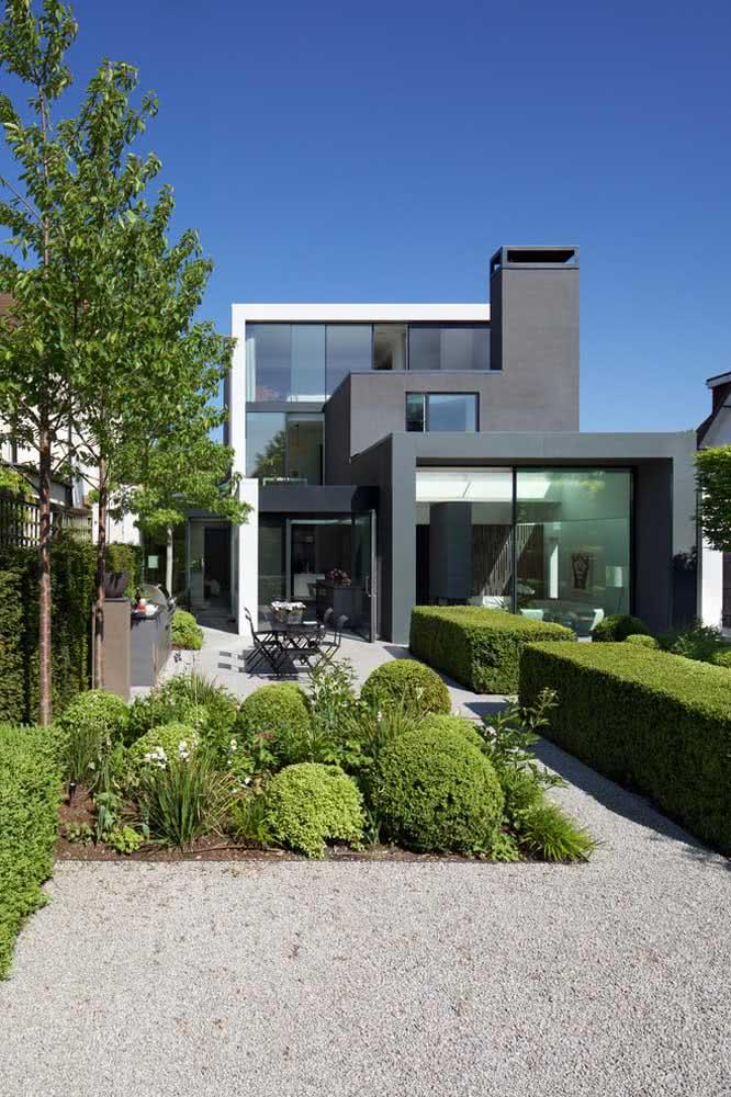 Esta residência utiliza a mistura entre as plantas e as pedras no decorrer da área externa.