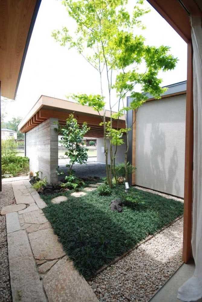 Área da entrada da residência com jardim e pedras no caminho até a porta de entrada.