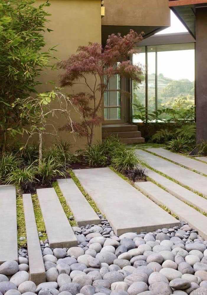 Aqui nesta residência, as pedras foram dispostas na lateral do caminho que conecta os ambientes.