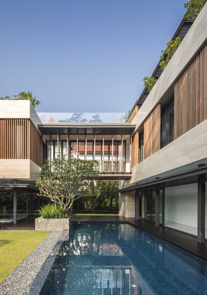 Casa moderna com jardim de pedras ao redor da piscina.