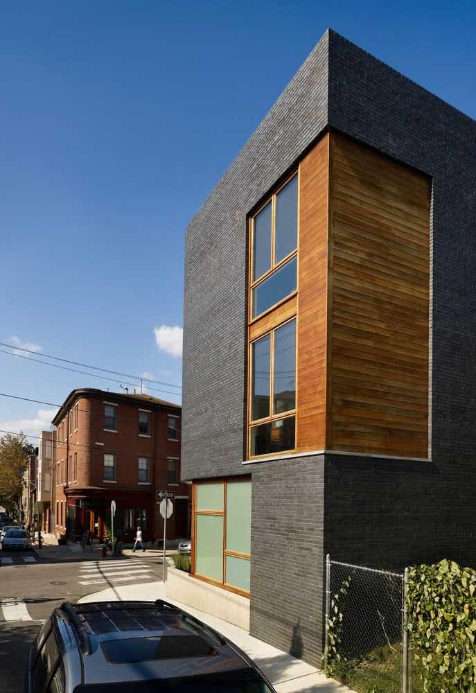 Casa moderna estreita de esquina com revestimento cinza e madeira nas áreas das janelas.