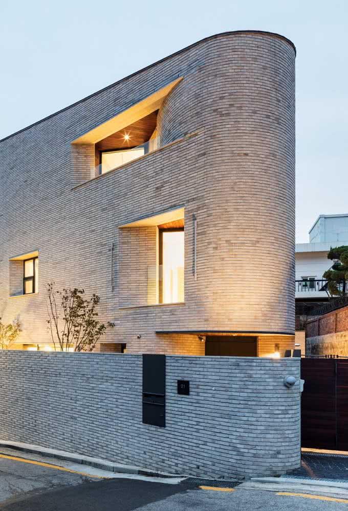 Modelo de casa estreita com parede curvada na extremidade. Aqui vemos revestimento de tijolos por toda a residência.