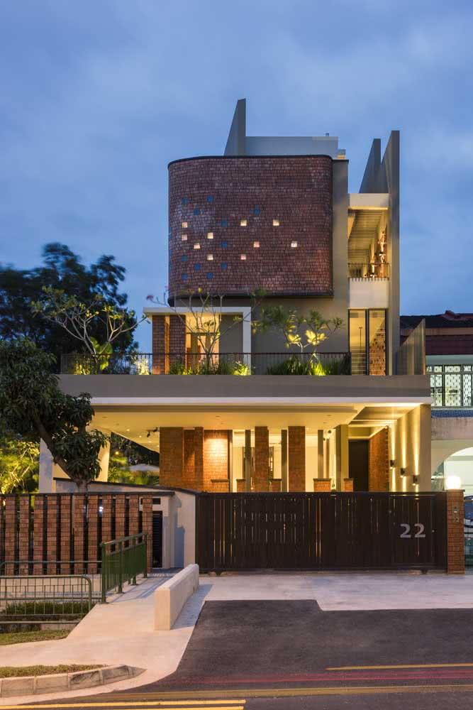 Fachada de casa grande de esquina com muro de tijolos vazado e portão metálico.