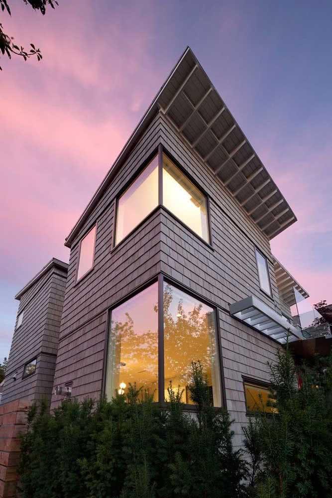 Casa de esquina com fachada revestida em madeira.