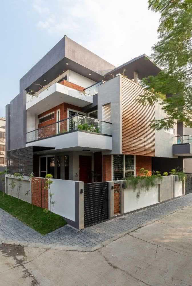 Casa de esquina com revestimento de madeira ripada na lateral, concreto e pintura branca.
