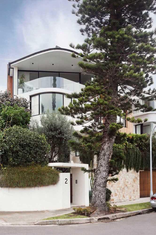 Casa de esquina com 3 pavimentos, muro branco e projeto de paisagismo.