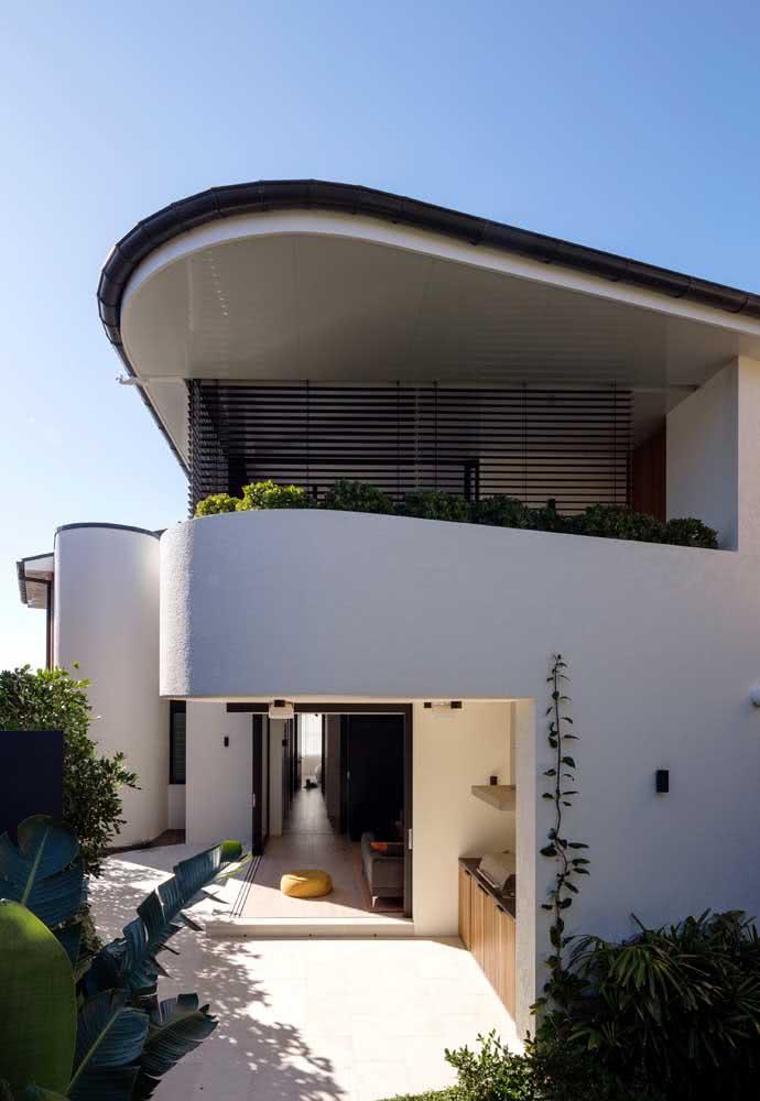Casa de esquina com varanda e parede curvada. A varanda foi construída no pavimento superior com vista para o quintal com jardim.