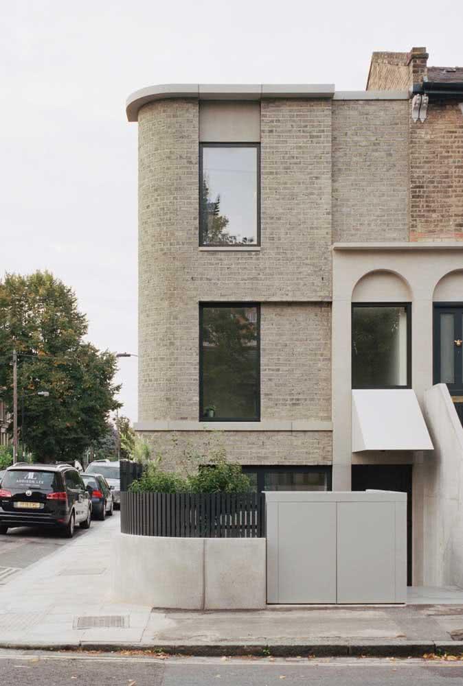 Casa de esquina americana com revestimento de tijolos claros e janelas de vidro.