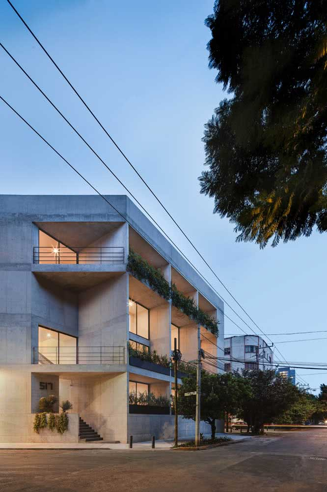 Construção residencial de esquina de concreto aparante com jardim.
