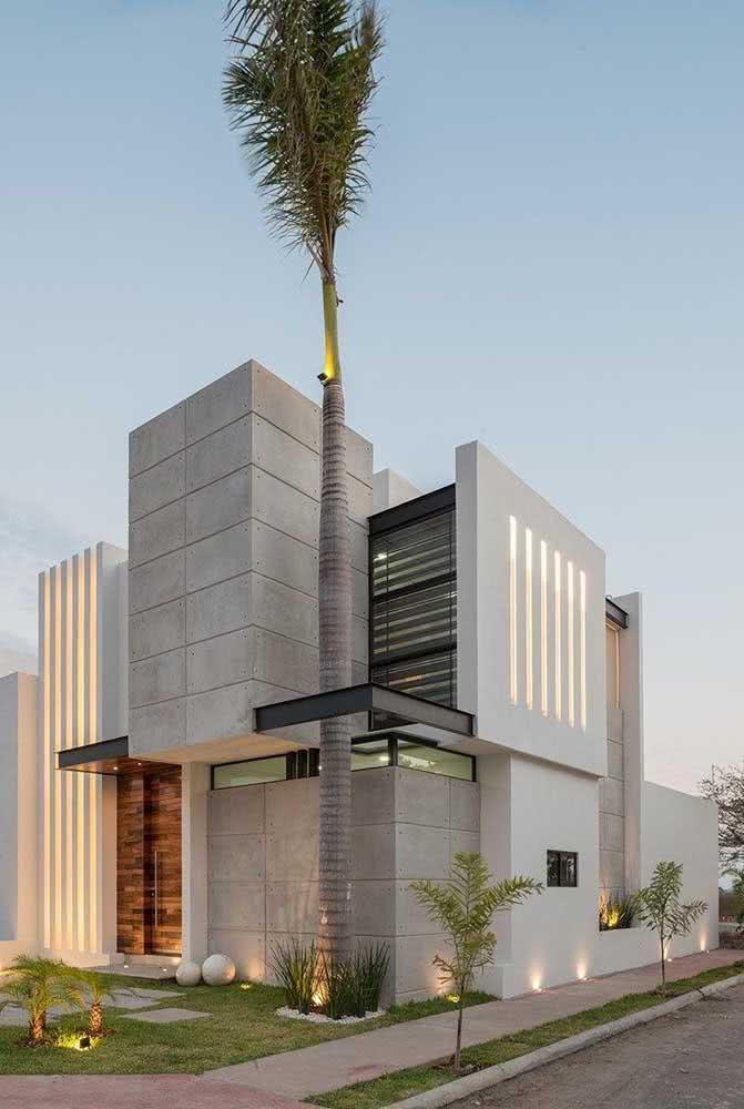Casa de esquina com dois pavimentos, detalhe da fachada com concreto, palmeira e metais.