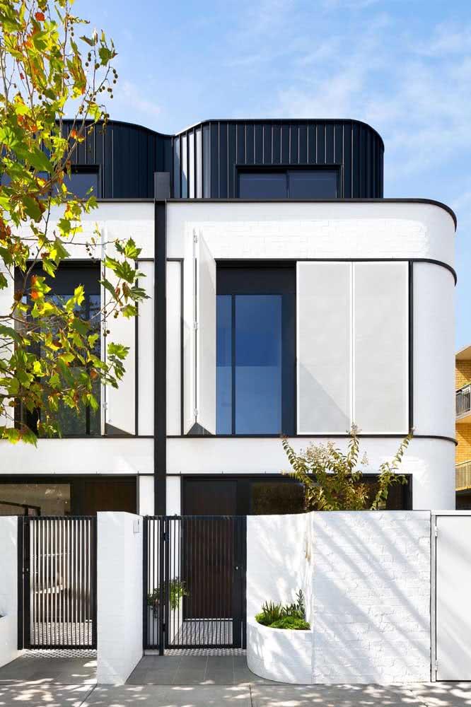 Casa geminada de esquina com pintura branca no muro de frente e na fachada.