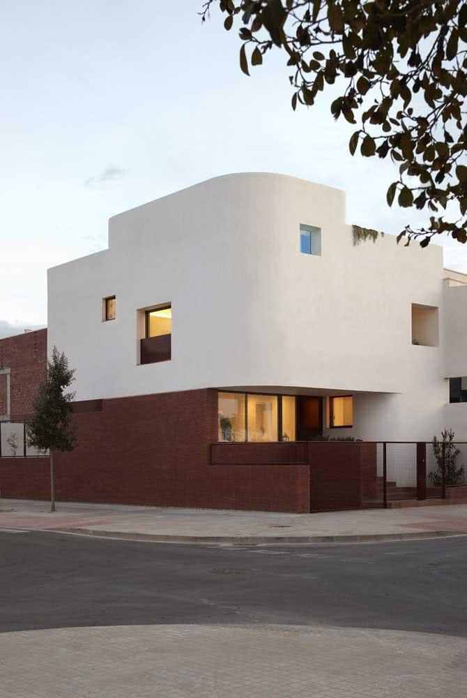 Casa de esquina com muro lateral de tijolinhos e portal metálico. O pavimento superior tem pintura lisa e curva redonda na extremidade.