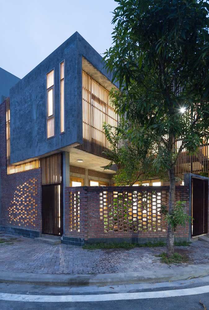 Casa de esquina com muro de tijolo vazado.