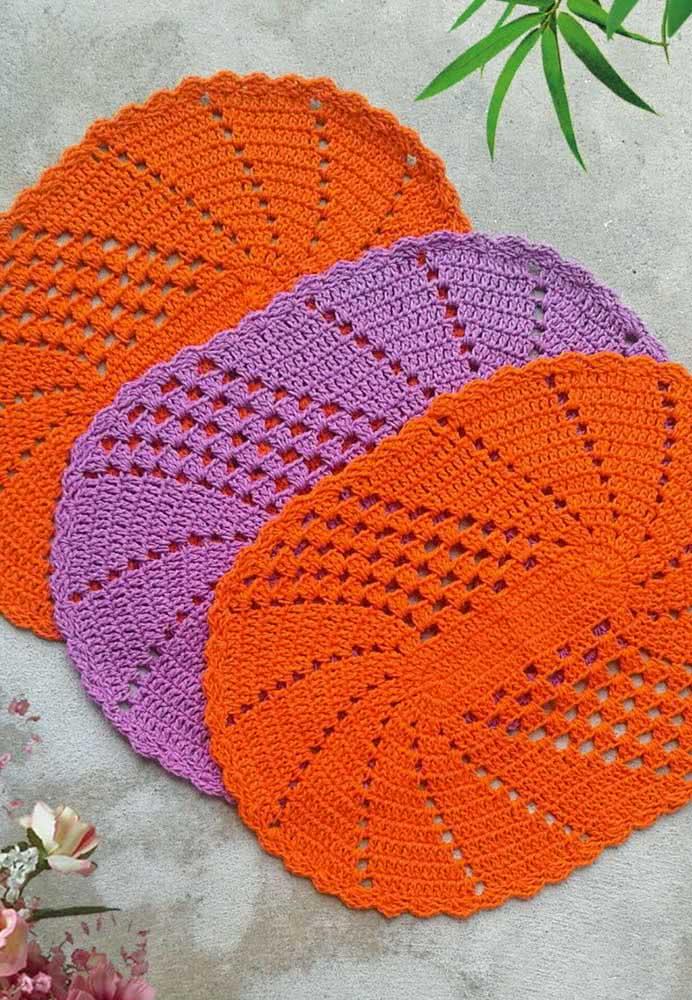 Trio de pequenos tapetes ovais com cores simples: laranja e lilás.