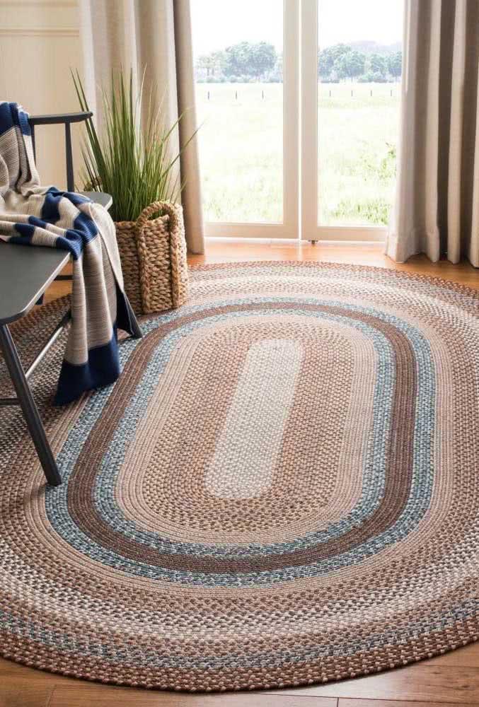 Tapete de crochê oval com mix de tons de marrom e azul.