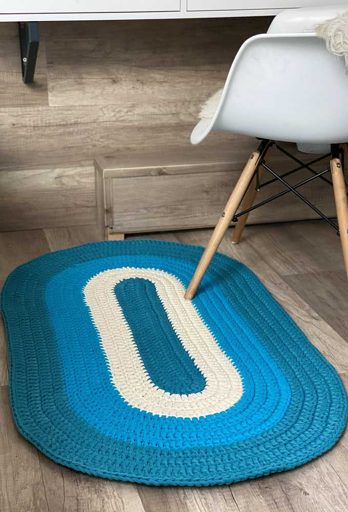 Tapete de crochê oval com tons de azul e branco.