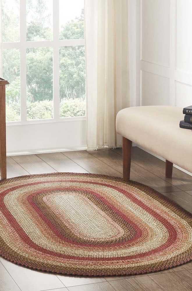Tapete de crochê oval com tons de palha, vermelho e marrom.