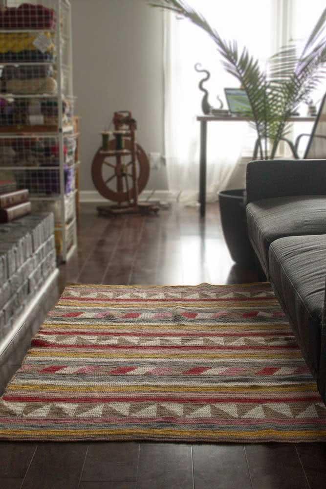 Tapete de crochê colorido e retangular com desenhos geométricos.