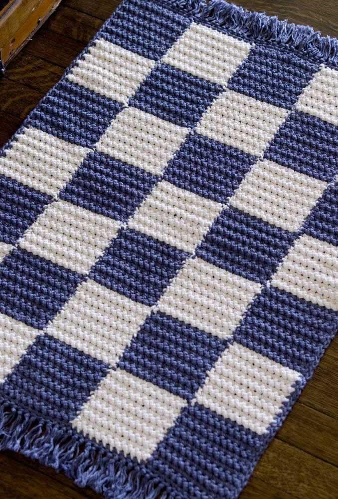 Tapete pequeno retangular todo quadriculado azul e branco.