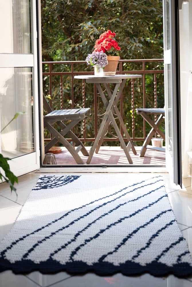 Tapete de crochê branco com listras azul marinho e outros desenhos.