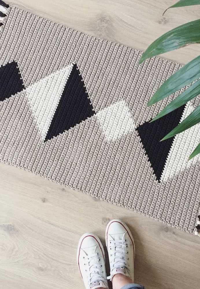 Tapete de crochê preto e branco com formas geométricas e base feita com barbante cinza.