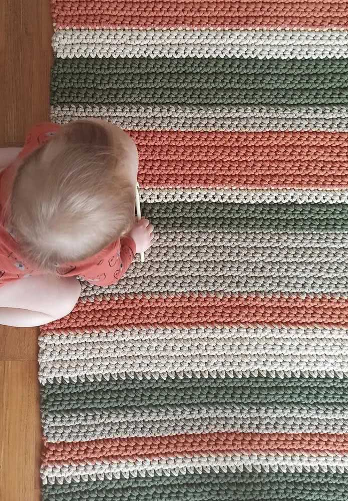 Listras vermelhas, brancas e verdes no tapete de crochê retangular para quarto de bebê.