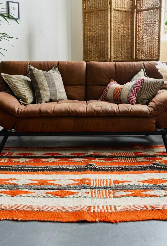 Tapete de crochê laranja para sala rústica com sofá de couro marrom.