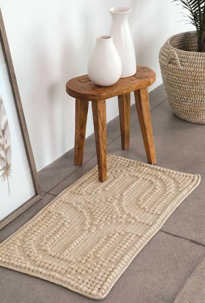 Tapete de crochê creme com desenhos em alto relevo feito com bolinhas.