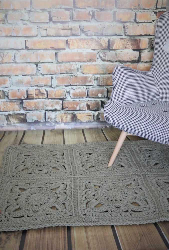 Tapete de crochê retangular cinza escuro com estampa vazada de flores.