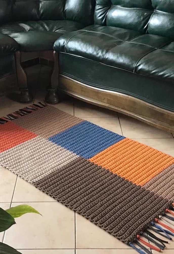 Tapete de crochê retangular com diversas formas quadradas em diferentes barbantes: azul, laranja, cinza, tons de marrom e vermelho.