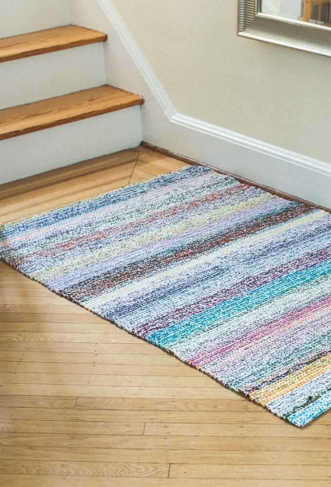Tapete de crochê com listras coloridas por toda a dimensão da peça.