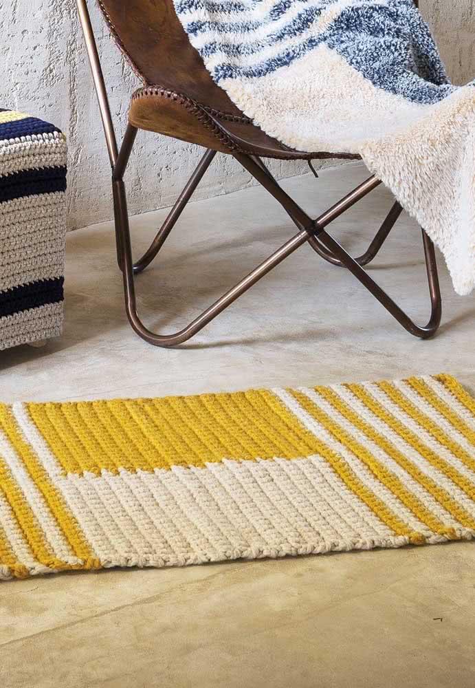 Listras amarelas em peça de crochê creme com barbantes grossos.