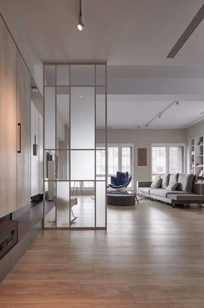 Esguia e elegante, essa divisória de vidro destaca o pé direito alto