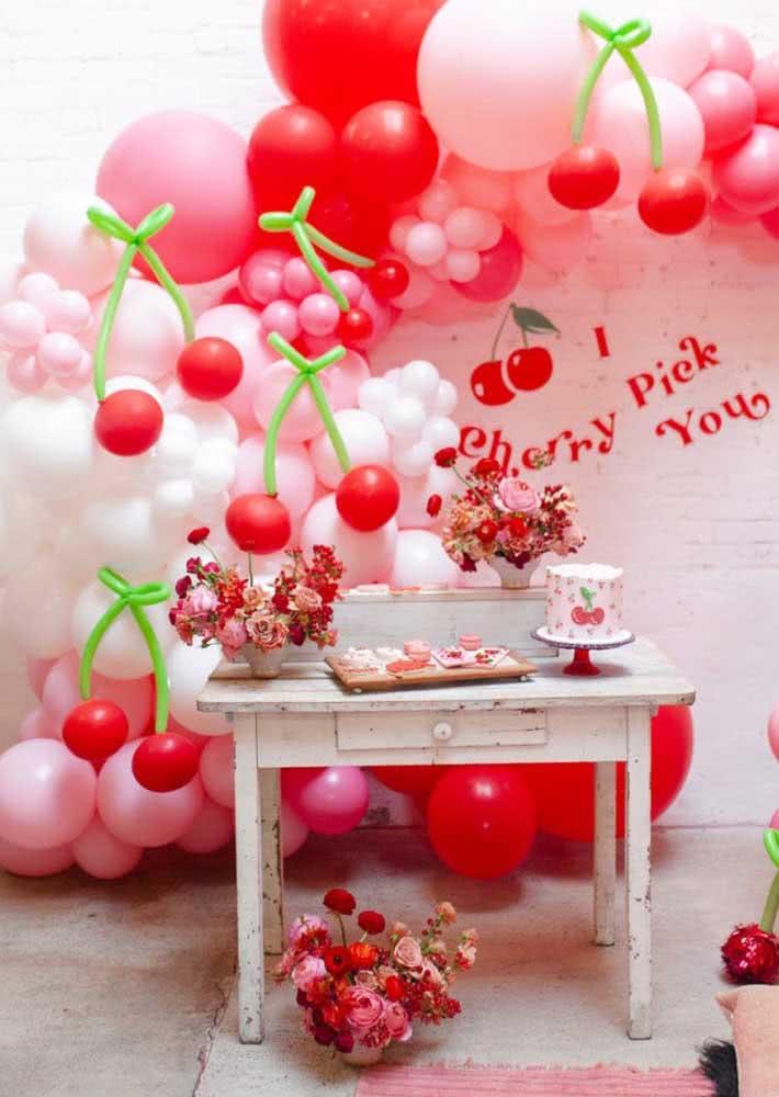 Mesa em estilo provençal decorada com flores e o bolo. O painel fica por conta dos balões em formato de cerejas