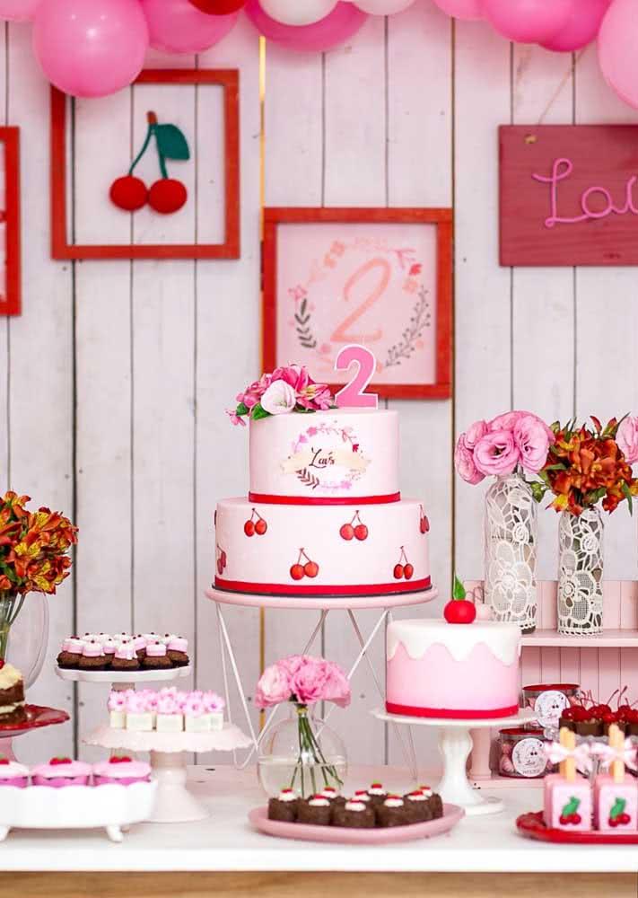 Mesa festa cereja decorada com doces e flores