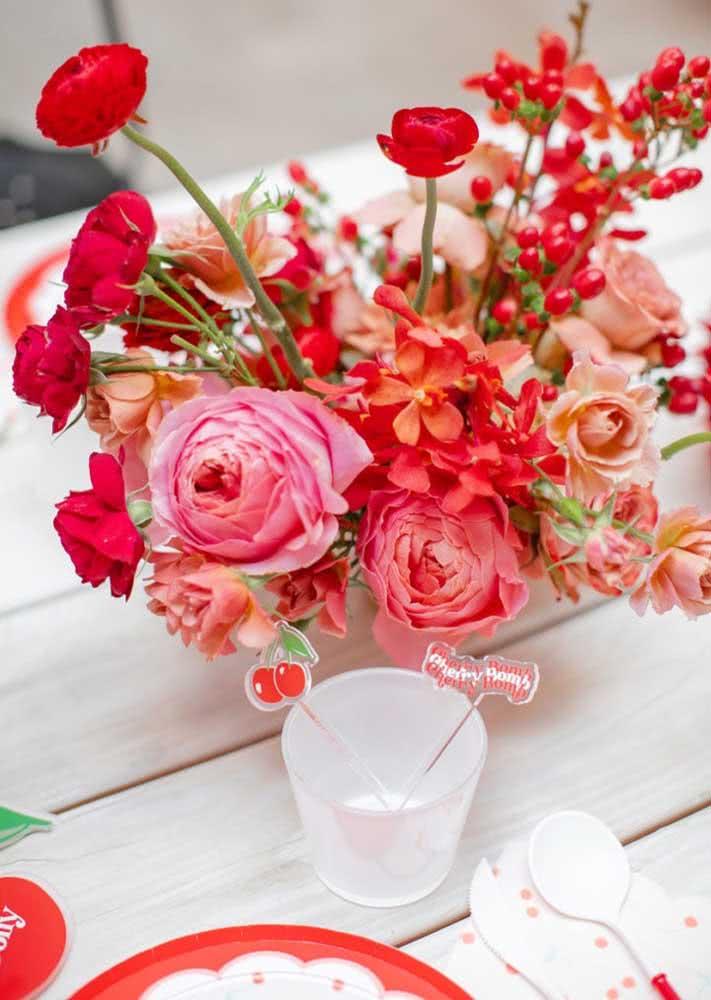 Flores nas cores do tema completam a decoração da mesa posta