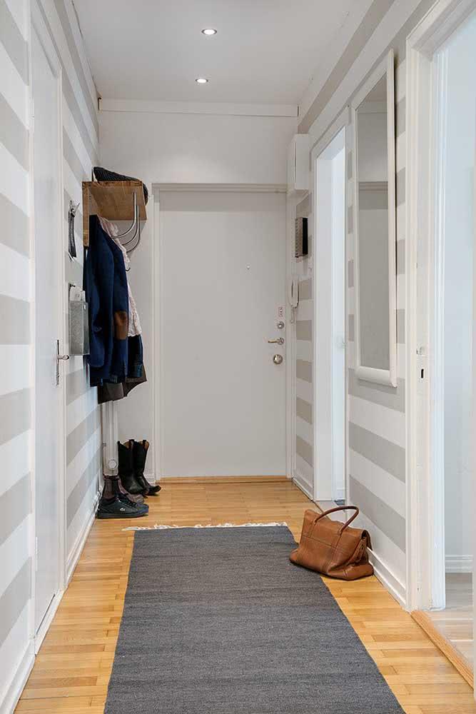 Papel de parede listrado horizontal favorece o comprimento do hall de entrada