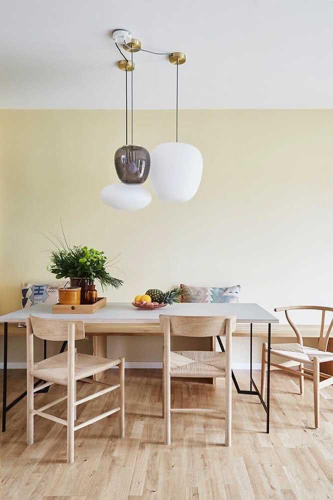 Parede amarelo pastel na sala de jantar. Aproveite para combiná-la com móveis de madeira clara