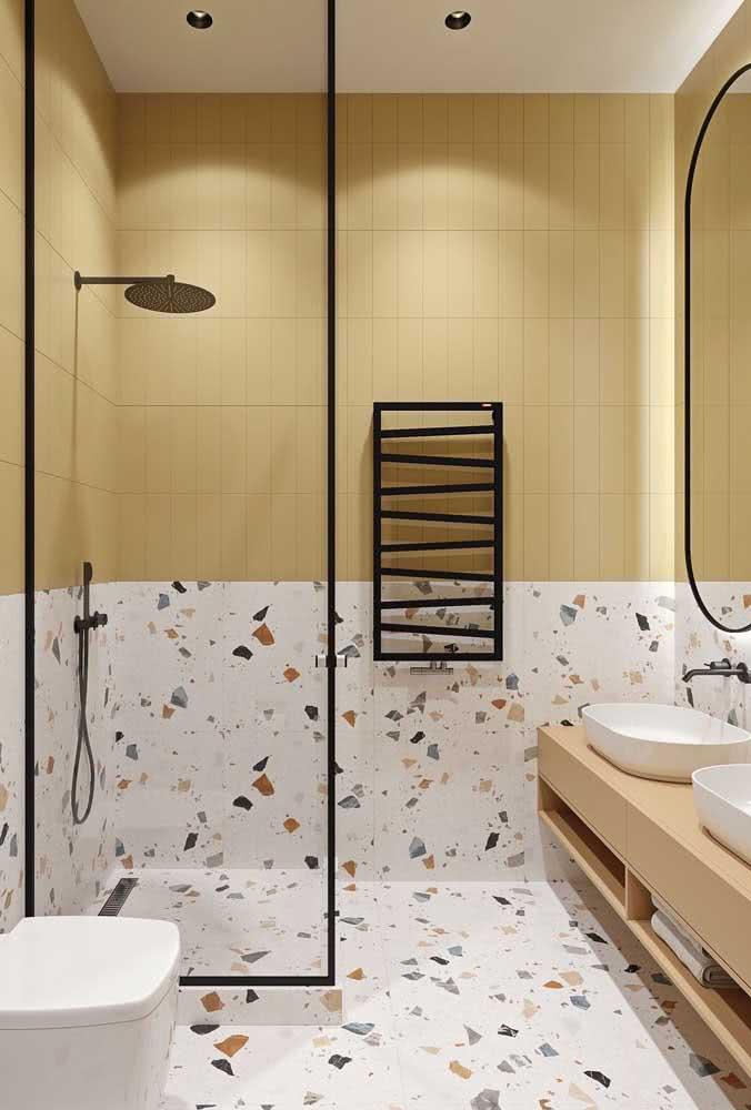 Granilite e azulejos amarelo pastel dividem o espaço da área do banho