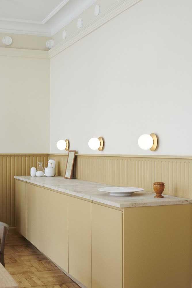Buffet e revestimento de madeira seguem o mesmo tom na sala de jantar