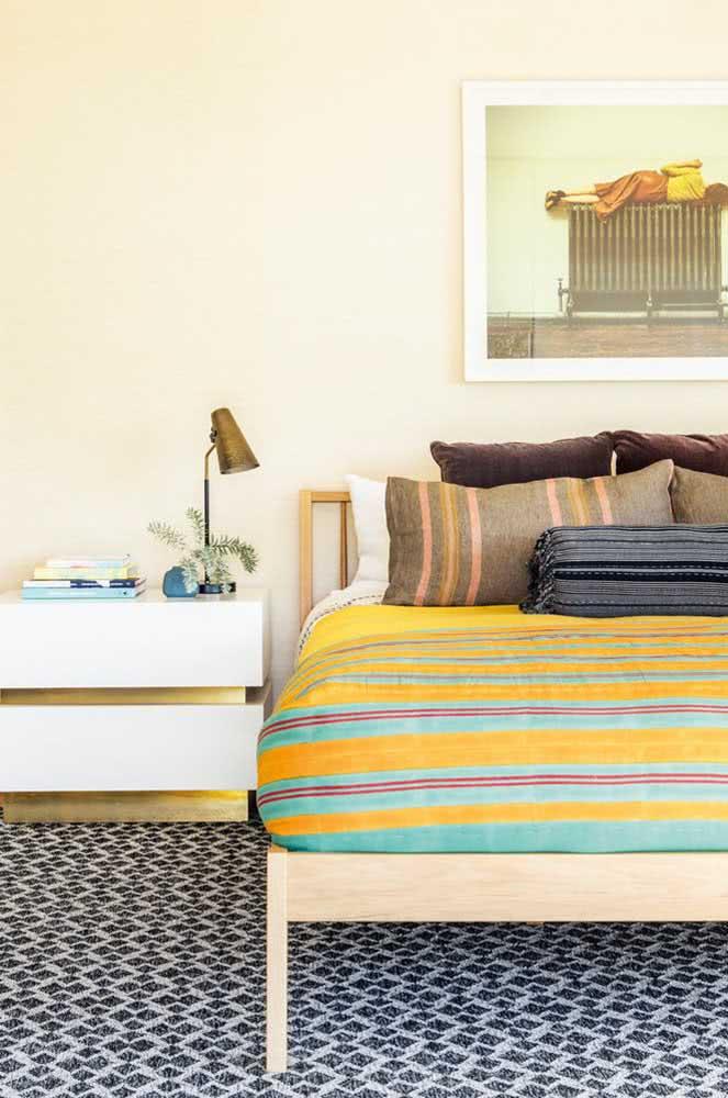 Parede amarelo pastel no quarto de casal acompanhando a paleta colorida do ambiente