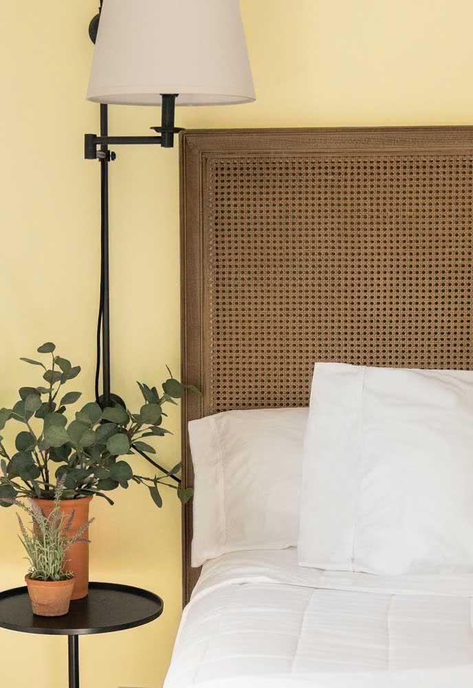 Quarto de casal rústico decorado com parede amarelo pastel e cabeceira de madeira